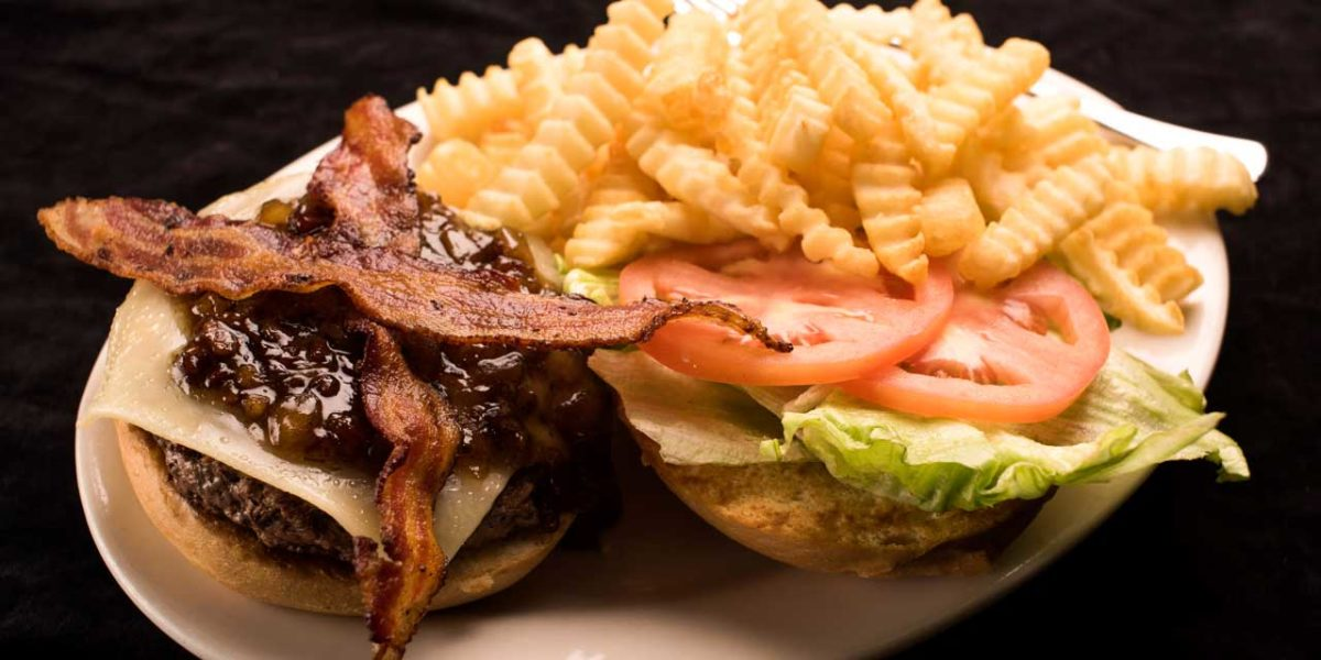 A delicious bacon cheeseburger served with crinkle-cut french fries.