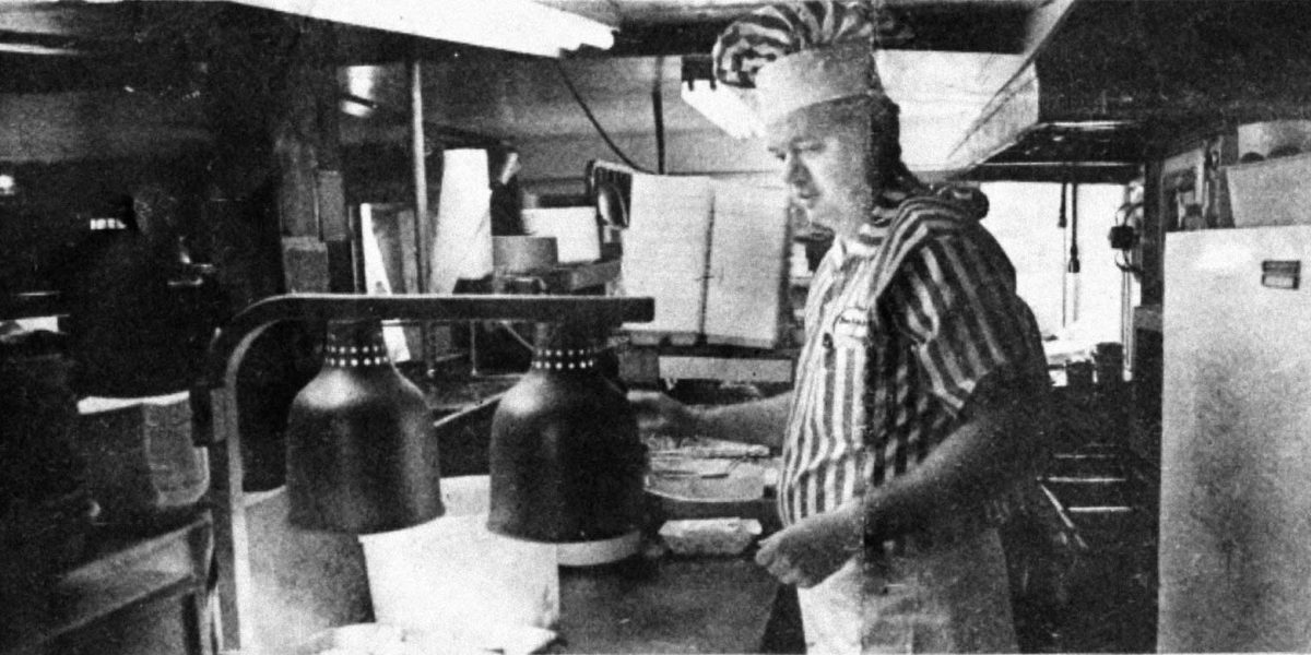 A black and white photo of Governor's founder Leith Wadleigh cooking a meal in Governor's original restaurant.
