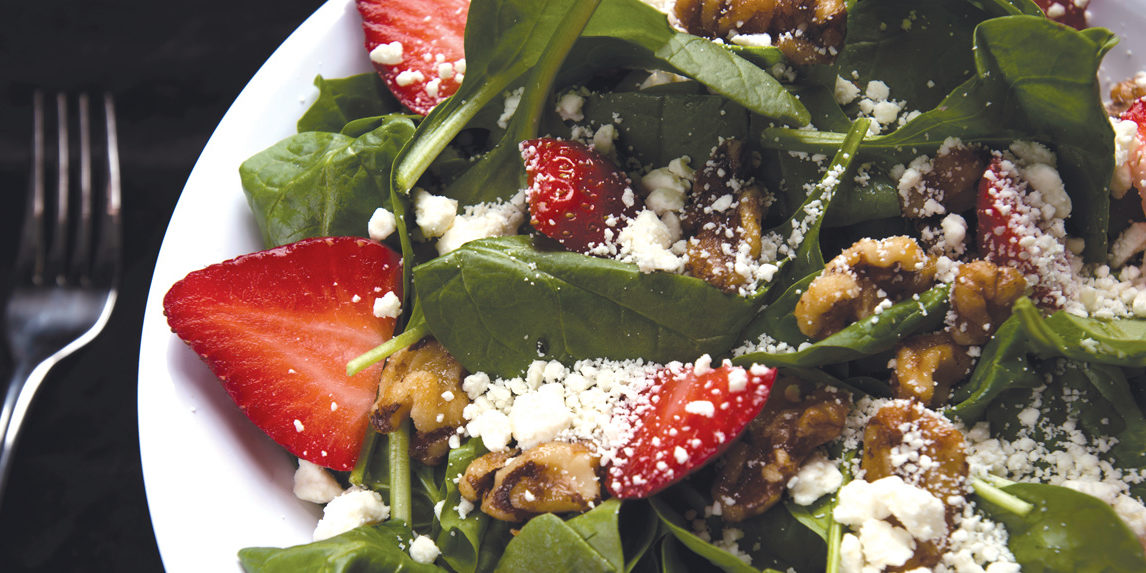 A crisp, fresh salad served with strawberries and feta cheese.