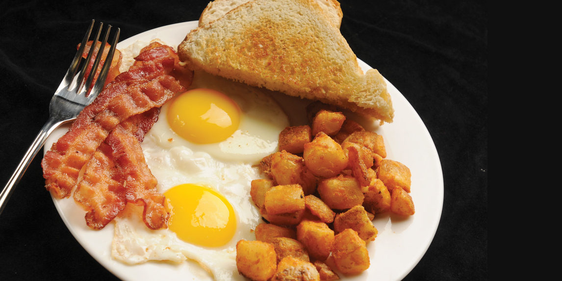 A full breakfast plate of seasoned eggs, home fries, toast, and bacon.